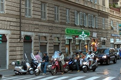 Scooters voor een stoplicht; Scooter-drivers waiting for a traffic-light