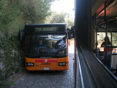 Twee bussen passeren elkaar op smalle weg.; Two busses passing on a narrow road.