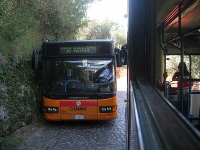 Twee bussen passeren elkaar op smalle weg.; Two busses passing on a narrow road.